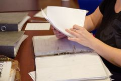 A person viewing the documents on the table in the living room, you can see hands and documents. Stock Photo