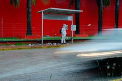 Person stands in the rain at bus stop while a car drives past him royalty free stock image