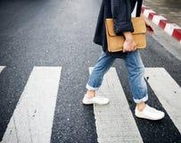 Person walking across the pedestrian lane Stock Photos