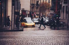 Person Walking Across the Street in Front of Yellow Sports Car during Daytime Royalty Free Stock Image