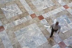 Person walking across a tiled floor Royalty Free Stock Photo