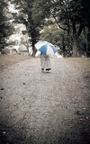 Person walking away in a rainy graveyard Stock Photo