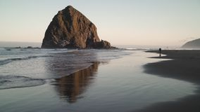 Solitary Walker by Haystack Rock, Cannon Beach 4K. UHD. A person walking the beach at dawn at Haystack Rock in Cannon Beach, Oregon, United States stock video