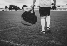 Person Walking on Field Holding Duffel Bag in Grayscale Photography royalty free stock images