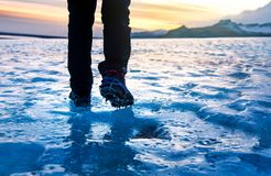 Person walking on glacier ice surface wearing crampons. Low angle royalty free stock image