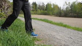 Person walking on gravel road stock footage