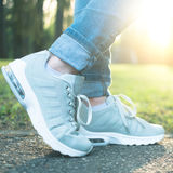 Person walking in gray running shoes, closeup Stock Photo