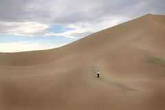 Person Walking on Large Sand Dune Stock Photo