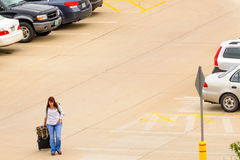 Person walking with luggage to the outdoor parking lot Royalty Free Stock Images