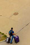 Person walking with luggage to the outdoor parking lot Stock Image