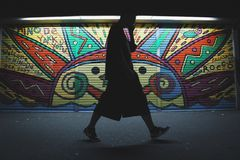 Person Walking Near Graffiti Wall Royalty Free Stock Photo