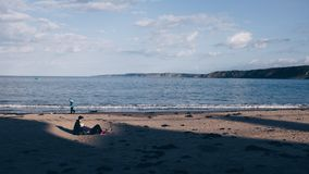 Person Walking Near Ocean Under White Sky Royalty Free Stock Photos