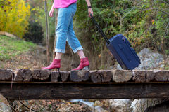 Person walking on old wooden bridge pulling Travel Suitcase Royalty Free Stock Images