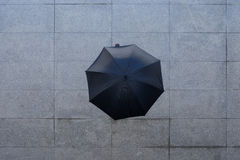When it rains. Person walking outdoors under black umbrella, view from the top stock image