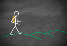 Person walking over hills. Drawing of a stick figure out of chalk at a blackboard showing a person hiking with a backpack having a walk over green hills, done by Stock Photo