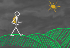 Person walking over hills. Drawing of a stick figure out of chalk at a blackboard showing a person hiking with a backpack having a walk over green hills with the Stock Photo