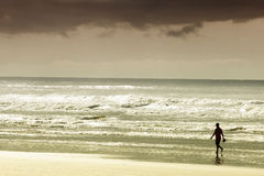 Person walking on sandy beach. With overcast cloudscape background Royalty Free Stock Photos
