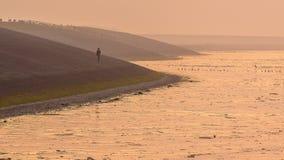 Person walking on Sea dike in orange haze Stock Images
