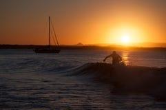 Person Walking In Sea Wave durante il tramonto Fotografia Stock Libera da Diritti