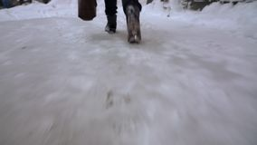 Person walking on snow covered ground. Camera following and chasing person feet while he is walking on snow covered ground to the house with a bag in one hand stock footage
