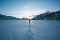 Person Walking in Snow Field Near Mountain Cliff Covered With Snow Stock Photos