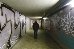 Person walking in subway underpass - light at the end of the tunnel - man walking alone in a potentially dangerous place Royalty Free Stock Photos
