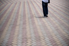 Person walking on tiled pedestrian road Stock Photos