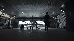 Person walking towards plane. Standing in hangar, view from behind stock footage
