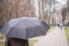Close-up of dark  umbrella during rain. Royalty Free Stock Image