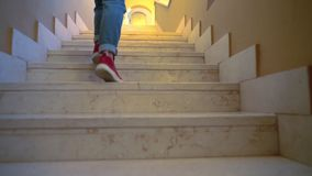 Person walking up indoor stairs at home. Person walking up a fight of narrow wooden indoor stairs at home in a low angle view of the legs in denim jeans stock video footage