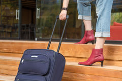Person walking up on wooden Stairs pulling Travel Suitcase Royalty Free Stock Image