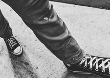 Person Walking Wearing Black Shoes in Grayscale Photography Royalty Free Stock Image