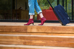 Person walking on wooden terrace pulling Travel Suitcase Royalty Free Stock Images