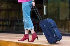 Person walking on wooden terrace pulling Travel Suitcase Royalty Free Stock Photo