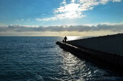 A person walks along the pier and leads the child`s hand stock images