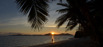 Person walks on the beach during tropical sunset Stock Images