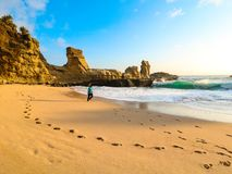 Person Walks on Brown Seashore Near Rock Formations Royalty Free Stock Photos
