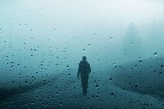 Person walks on foggy road during rainfall stock images