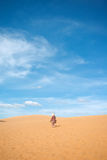A person walks on the red sand dunes. Mui Ne, Vietnam Royalty Free Stock Image