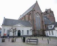 Person walks on small old square near church in wijk bij duurstede. Wijk bij duurstede, netherlands, 23 january 2018: person walks on small old square near Stock Image