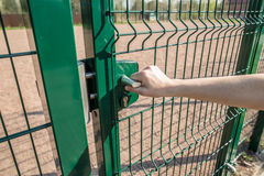 Person wants get in on playground through the little gate of wel. Person wants get in on playground through the little gate of the welded wire mesh is green Stock Photo