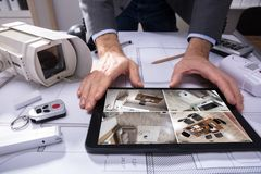Person Watching Footage On Digital Tablet. With Security Equipments On Blueprint stock photo