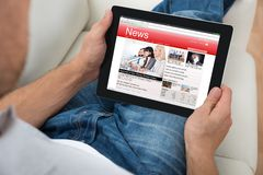 Person Watching News On Digital-Tablet Stockfotos