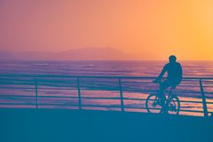 Person watching the sunset on bike. Person watching the sunset on the bike royalty free stock photography