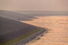Person watching sunset from Sea dike in orange haze. Person watching sunset from Delta works Sea dike of the Waddensea in orange haze around sunset in Friesland Stock Photo