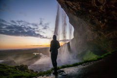 Person at waterfall at sunset Stock Photos