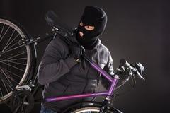 Person Wearing Balaclava Stealing una bicicletta fotografie stock libere da diritti