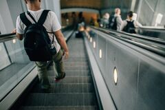 Person Wearing Black Backpack Riding Down the Escalator Stock Image