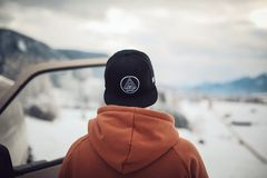 Person Wearing Black Cap and Orange Hoodie Turning His Back Royalty Free Stock Image