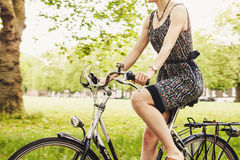 Person Wearing Black and Gray Sleeveless Dress Riding a Step Through Bicycle Stock Photography